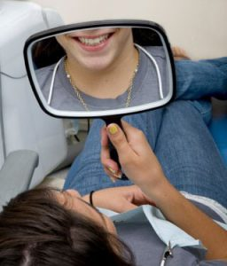 dental patient looking at smile in mirror