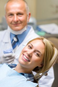 woman smiling at the dentist after an exam