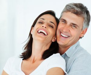 man standing behind woman smiling and leaning into him